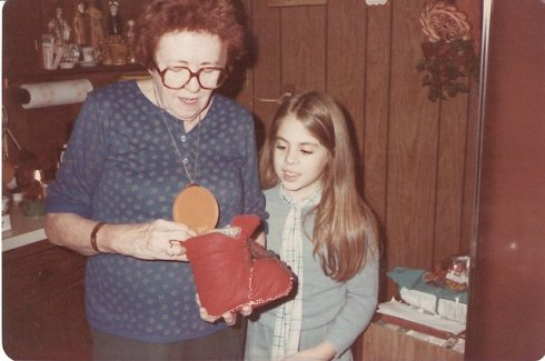 Grandma Marie being very gracious as I give her the coffee can Santa boot cookie jar that I made with my mom's help...